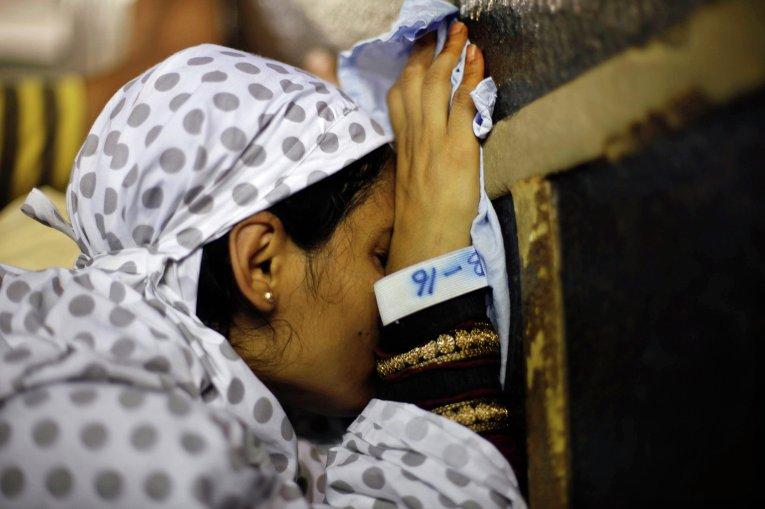 Мусульманские паломники прикасаются к Каабе в Большой мечети Мекки
