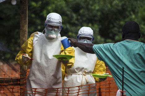 Медицинские работники, сотрудничающие с организацией «Доктора без границ», раздают еду пациентам Центра по лечению вируса Эбола в Кайлахуне