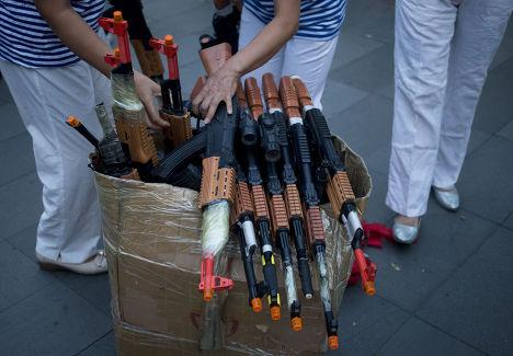 Женщины разбирают игрушечне автоматы перед пением революционных песен в центре Пекина
