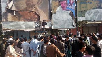 Сторонник Талибана снимает портреты афганских лидеров со стены на главной площади города Кундуз