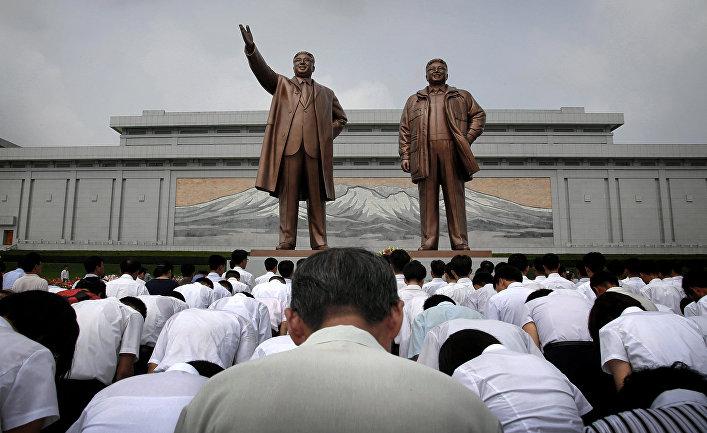 Корейцы у памятников Ким Ир Сена и Ким Чен Иру во время празднования 62-летия окончания Корейской войны