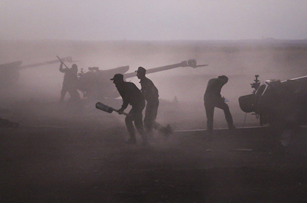 Военнослужащие сирийской армии загружают гаубицы рядом с деревней Морек