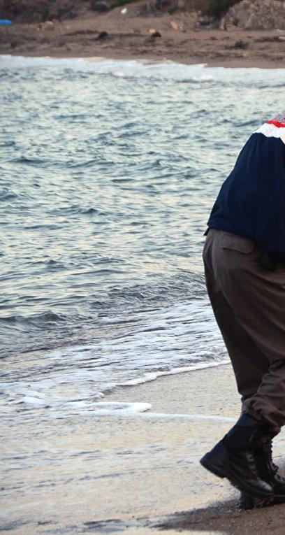 Полицейский несет тело трехлетнего Айлана Курди