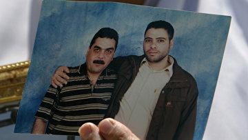 Женщина с портретом своего сына, заключенного израильской тюрьмы, сфотографированного вместе с лидером друзской террористической группировки Самиром Кунтаром