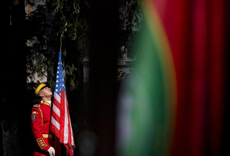 Румынский солдат держит флаг США во время церемонии открытия командного центра НАТО в Бухаресте