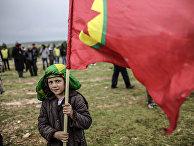 Мальчик из семьи сирийских курдов держит флаг Курдистана во время празднования Навруза в городе Кобани