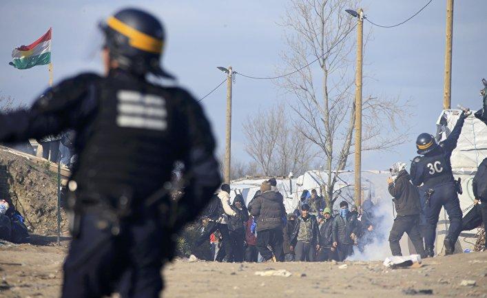 """Сотрудники полиции во время беспорядков в лагере мигрантов """"Джунгли"""" возле Кале, Франция"""