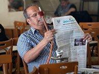 Посетитель кальянной в Дамаске читает газету