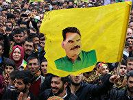 Сторонник Рабочей партии Курдистана держит флаг с портретом ее лидера Абдуллы Оджаллана во время празднования Навруза в городе Диярбакыр