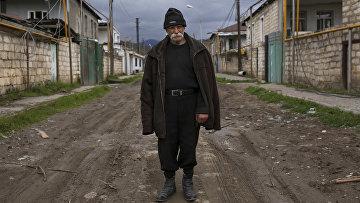 Местный житель возле брошенных и разрушенных боевыми действиями домами недалеко от города Мардакерт