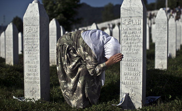 Женщина у могилы родственника в мемориальном комплексе Поточари под Сребреницей