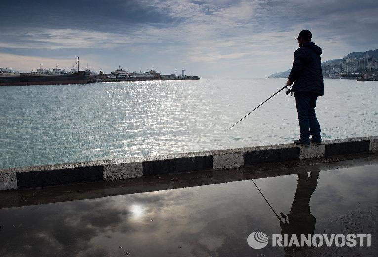 Рыбак на набережной Ялты