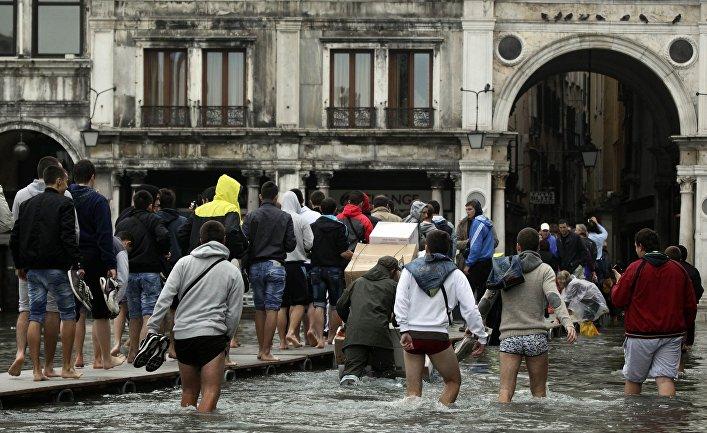 Туристы в Венеции во время сезонного паводка