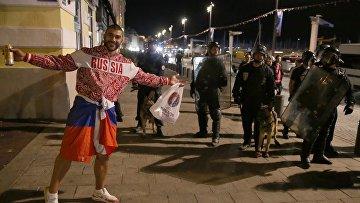 Российский болельщик возле полицейских на одной из улиц Марселя после окончания матча группового этапа чемпионата Европы по футболу — 2016 между сборными командами Англии и России