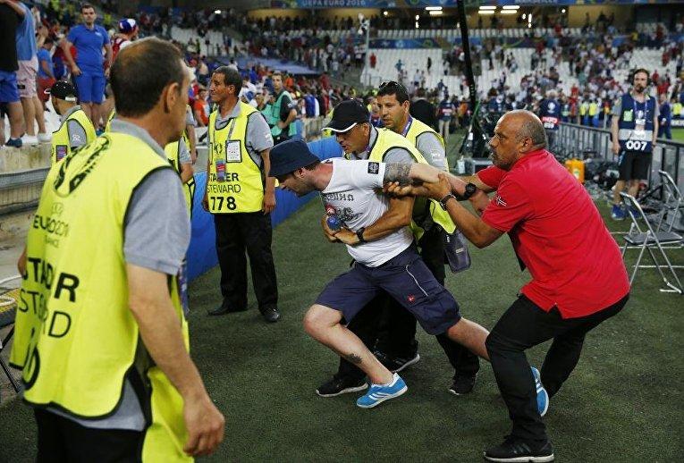 Сотрудники службы безопасности стадиона задерживают фаната во время беспорядков