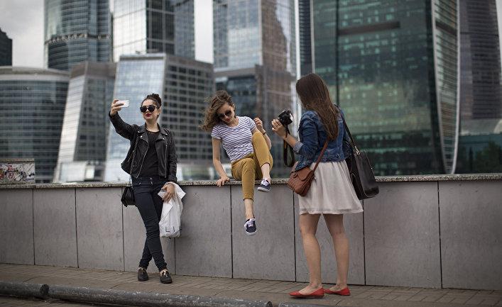 Девушки фотографируются на фоне небоскребов «Москва-Сити»