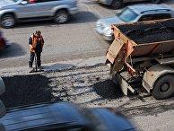 Рабочий во время ремонта дорожного покрытия на улице Кирова в Омске