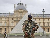 Солдат патрулирует внутренний двор Лувра
