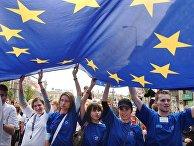 Молодые люди несут флаг Европейского союза во время парада Шумана в Варшаве