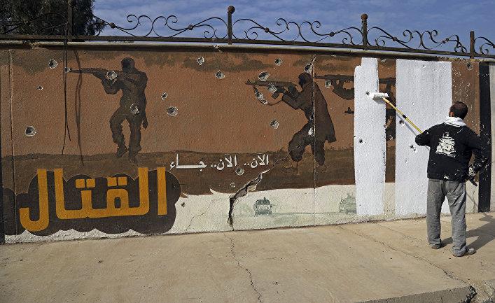 Волонтер закрашивает граффити, оставленное ИГИЛ (запрещена в РФ) в Мосуле