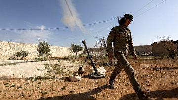 Боевик стреляет из миномета в сторону солдат сирийской армии, на западе от города Манбидж