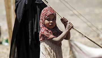 Йеменская девочка ждет поставки гуманитарной помощи российской гуманитарной миссии в лагере на окраине столицы Саны