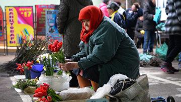 Пожилая женщина продает цветы на местном рынке в Тирасполе