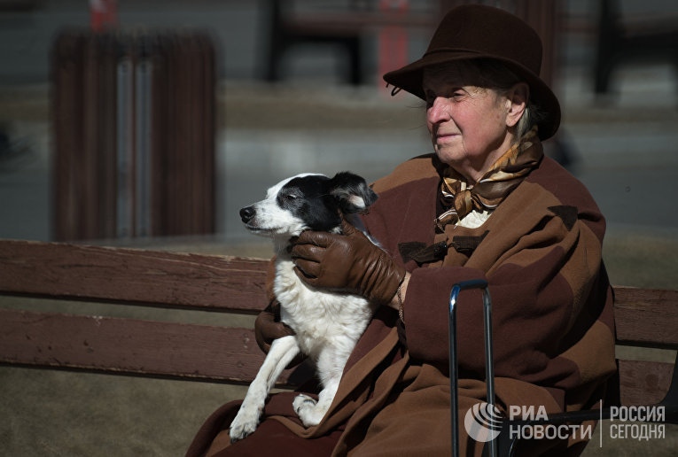 Пожилая женщина сидит на скамейке