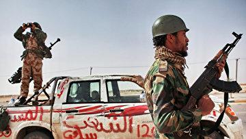 Боец оппозиции и наблюдатель с биноклем в городе Аждабия