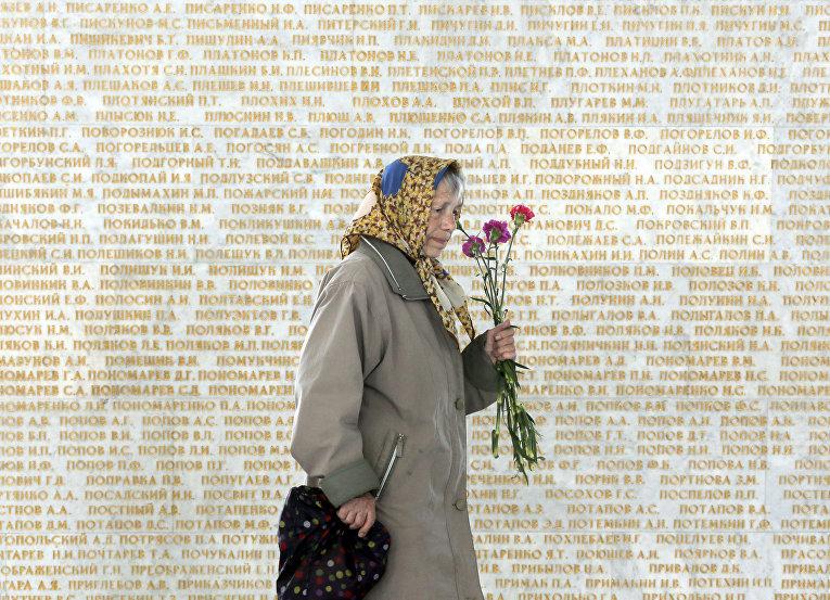Женщина на фоне стены с именами погибших в Великой отечественной войне в Киеве