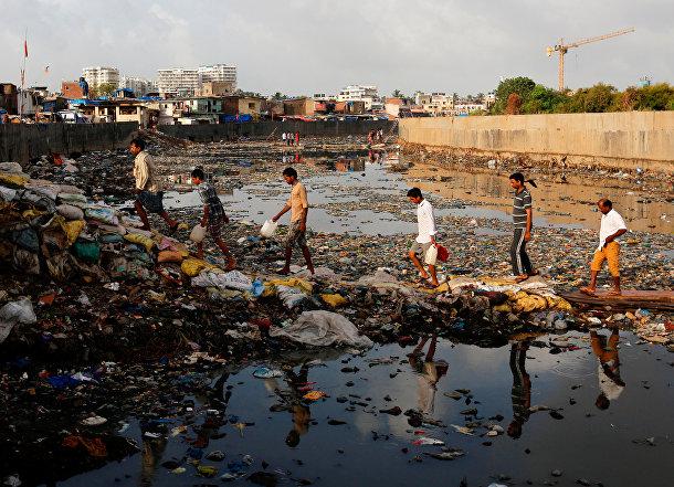 Жители индийского Мумбаи пересекают загрязненный канал в трущобах города