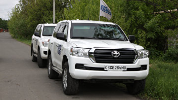 Автомобили ОБСЕ на месте артиллерийского обстрела Куйбышевского района Донецка