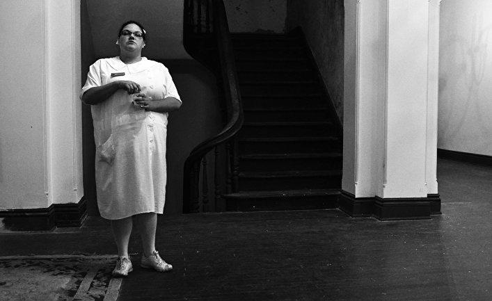 Экскурсовод, одетая как медсестра в главном здании психиатрической больницы Транс-Аллегейни в Вирджинии
