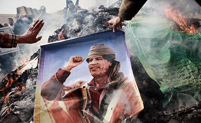 """Портрет Муамара Каддафи, плакаты с его цитатами и """"Зеленая книга"""" Каддафи"""