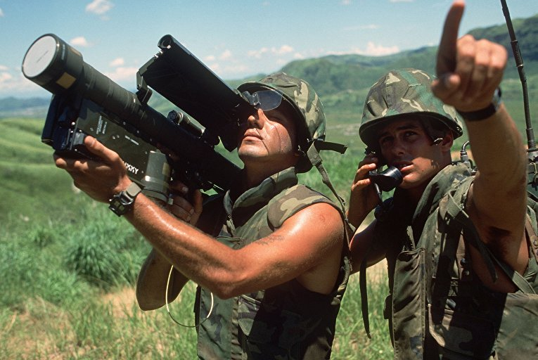 Морской пехотинец США с полевой радиостанцией передаёт направление ЛА оператору ПЗРК FIM-92 Stinger (1984).