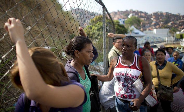 Люди стоят в очереди, чтобы купить продукты в Каракасе