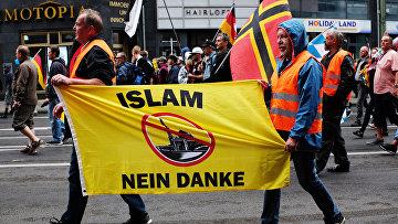 Участники акции против про-иммигрантской политики канцлера Германии Ангелы Меркель в Берлине. 2 июля 2017