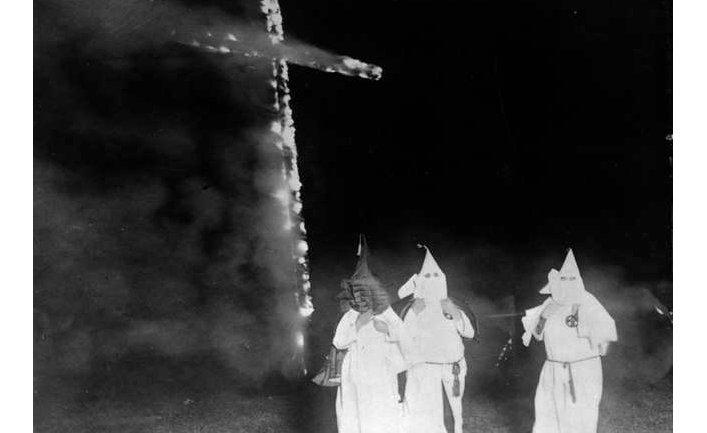 Члены организации «Ку-клукс-клан» на фоне символа «горящего креста»
