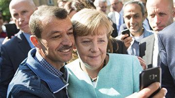 Канцлер Германии Ангела Меркель фотографируется с беженцами в Берлине