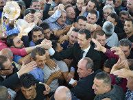 Президент Сирии Башар Асад приветствует сирийцев после молитвы в мечети Билал в городе Каламун, Сирия