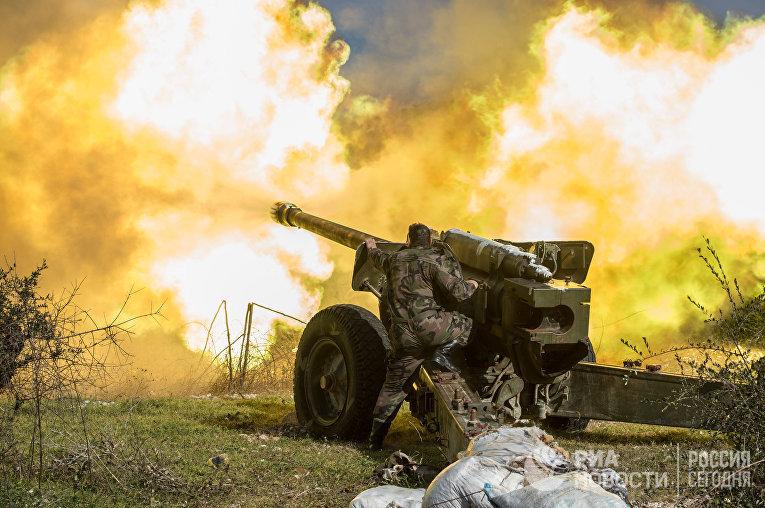 Артиллеристы сирийской армии ведут стрельбу на позициях в провинции Идлиб на северо-востоке Сирии