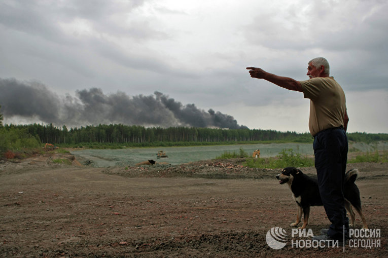 Местный житель отвечает навопросы журналистов вовремя пожара наполигоне токсичных отходов «Красный бор» вЛенинградской области