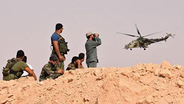 Сирийские военные наблюдают за полетом российского военного вертолета на окраине города Дейр-Эз-Зора