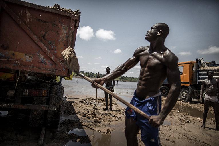 Рабочий в карьере на берегу реки Конго
