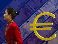 Девушка проходит мимо знака евро на выставке, посвященной валюте в Пекине
