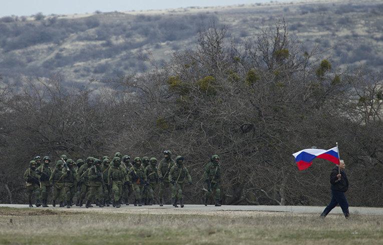 Местный житель с флагом и российские военные рядом с украинской военной базой в деревне Перевальное под Симферополем