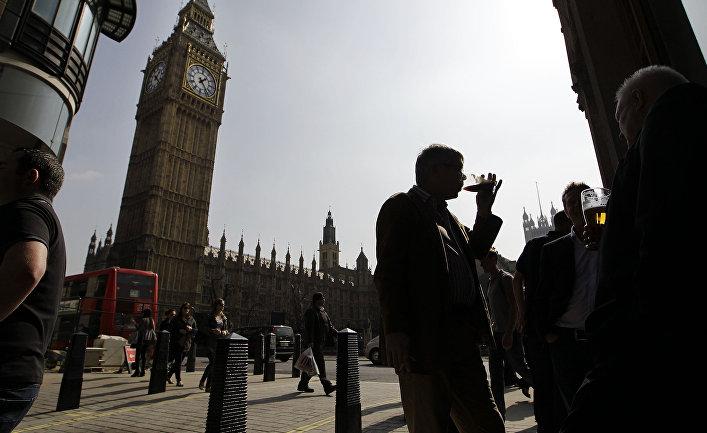 Люди наслаждаются пивом у паба напротив парламента в Лондоне