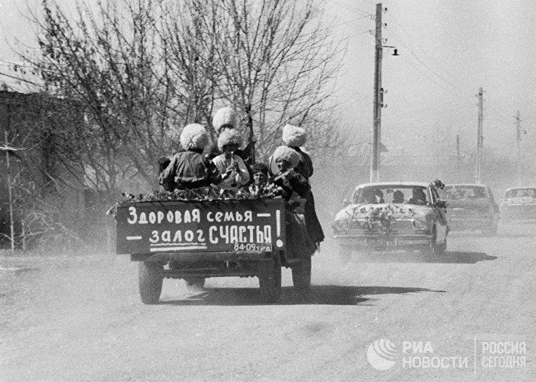 Свадебный кортеж едет по улице туркменского поселка