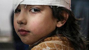 Раненая сирийская девочка после бомбардировок в Восточной Гуте