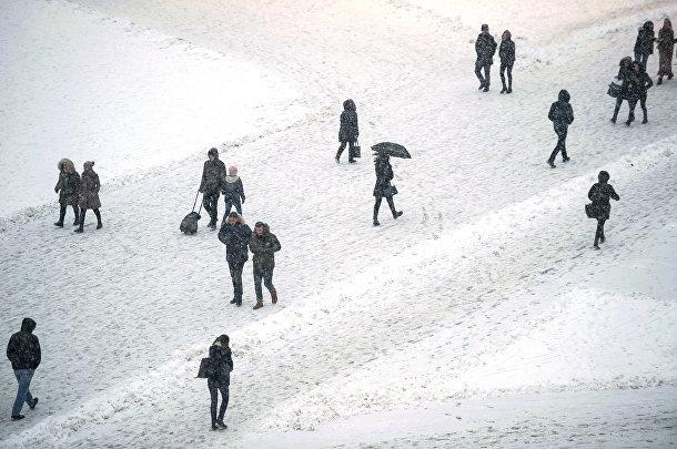 Люди идут по заснеженной площади в Приштине, Косово